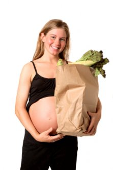 Young pregnant woman with a healthy bag of groceries