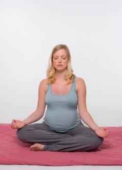 pregnant woman meditating and doing yoga